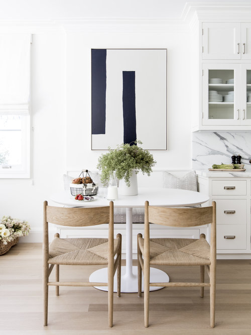 A Modern White Oval Dining Table Is Paired With Rush Seat Dining Chairs.