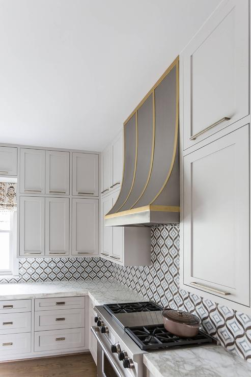 Steel And Brass Kitchen Hood With White Shaker Cabinets