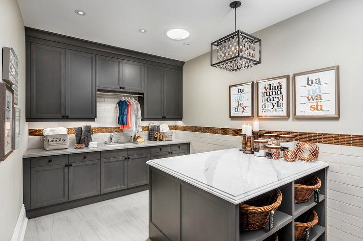 Stunning Laundry Room Features A Crystal Cage Chandelier Hung Above A Gray  Island Fitted With Shelves Holding Wicker Hamper Baskets And A Gray And  White ...