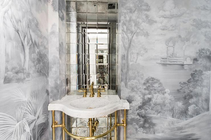 Elegant Contemporary Powder Room Features A Honed White Marble And Polished Brass Washstand Completed With A Round Sink Paired With A Polished Brass Faucet