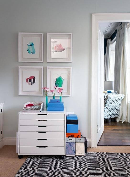 pale blue home office walls in farrow u0026 ball pale powder are accented with colorful framed art pieces hung above an ikea alex drawer unit on casters placed