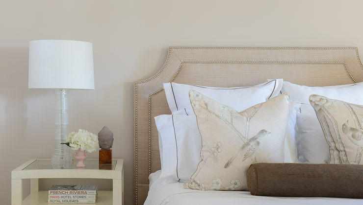 a beige belgrave shaped headboard frames a bed with nailhead trimming adorned with hummingbird and blossom pattern accent pillows