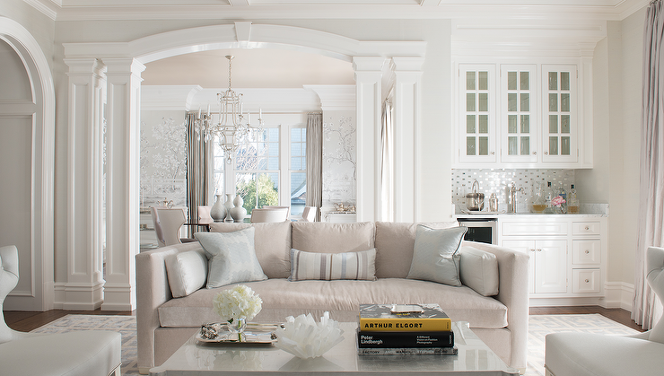 A Gray Sofa Is Accented By Silver Metallic Pillows In Room With Column Walls And Fine Molding