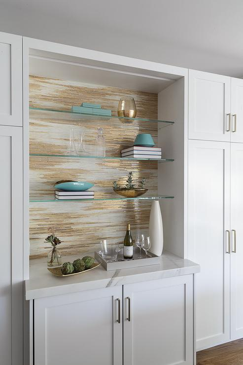 Gray And Gold Metallic Wallpaper Is Fixed Behind Stacked Glass Front  Shelves Mounted Above White Shaker Bar Cabinets Accented With Brass Hardware  And A ...