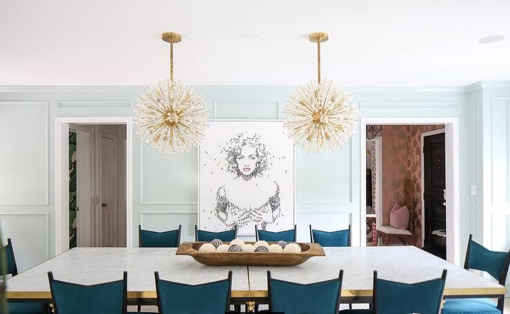 Elegant Contemporary Dining Room Is Illuminated By Two Brass Sputnik  Chandeliers Hung Over A Large Marble Top Dining Table Accented With A Brass  Trim And ...