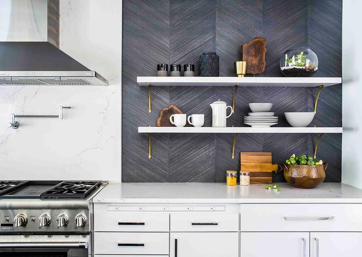 Stacked White Shelves With Brass Brackets Are Mounted To A Wall Covered In  Dark Gray Chevron Tiles Above White Flat Front Cabinets Finished With  Polished ...