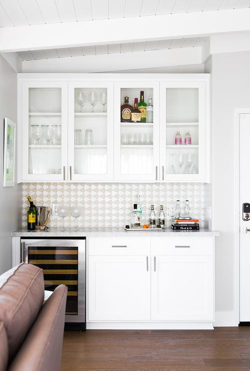 A Living Room Bar Nook With White And Gray Mosaic Tiles Features A Built In  Wine Cooler In The Lower Cabinet Space.