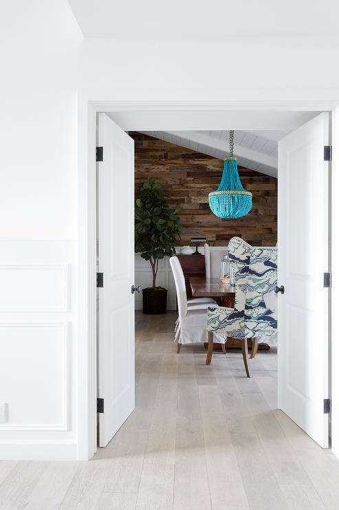 Dining Room With Sloped Ceiling And Wood Plank Wall