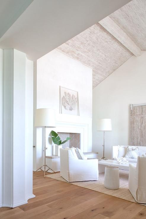 Under A Gray Wash Plank Ceiling, A White Cottage Living Room Boasts A High  Back White Slipcovered Sofa Positioned On A Jute Rug Facing A White  Waterfall ...