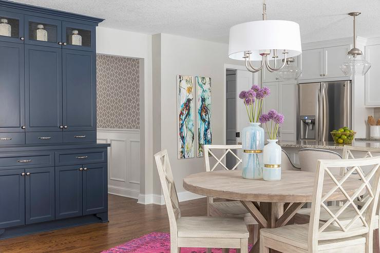 A Blue Hutch And Sideboard Beautifully Complements Round Trestle Dining Table Placed Beneath White Drum Light Pendant Surrounded By Trellis Back
