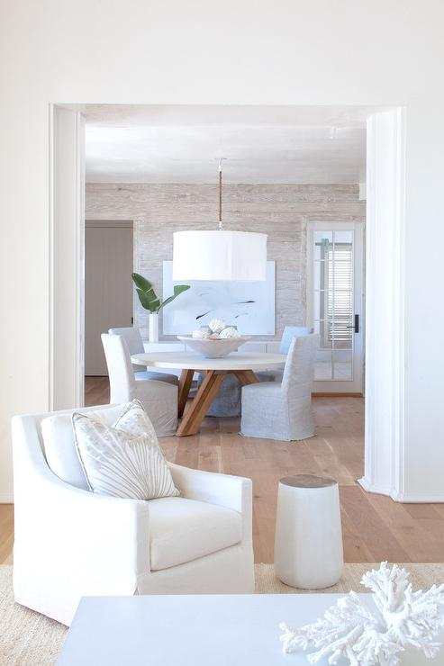 a canvas art piece is mounted on a gray wash oak plank wall behind a round white dining table illuminated by a rope and white linen drum pendant and seating