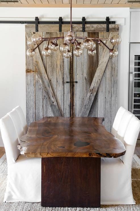 A Rustic Barn Door On Rails Is Positioned Beneath Plank Ceiling Facing Live Edge Dining Table Flanked By White Slipper Chairs Placed Bound Jute Rug