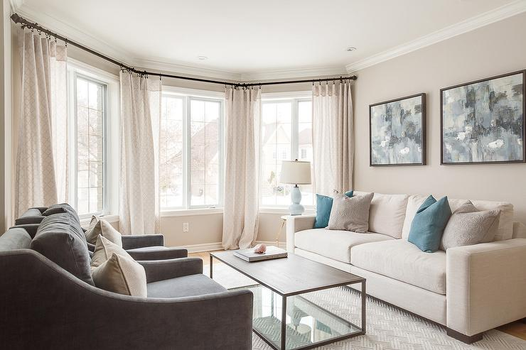 amazing Living Room With Cream Sofa Part - 8: Welcoming living room features bay windows dressed in cream curtains  complementing cream colored walls and a cream modern sofa topped with blue  and gray ...