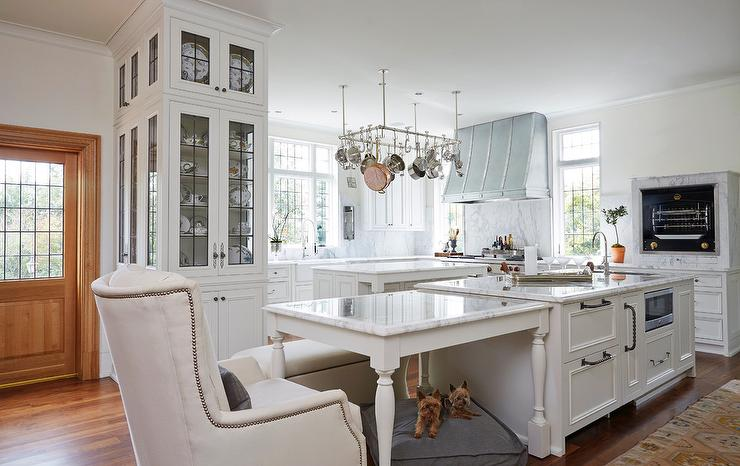 A Cooks Kitchen Features An Island Fitted With Microwave Topped White Marble Placed Directly Next To Top Dining Table Lined