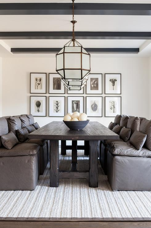 Stylish Dining Room Is Illuminated By Suzanne Kasler Morris Lanterns Hung Over A Dark Wood Stained Table Flanked Gray Leather Slipper