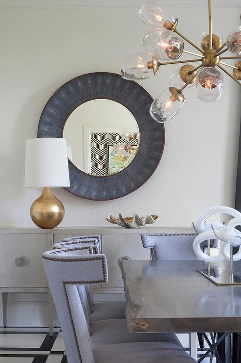 An Aerin Warren Table Lamp Sits Atop A Gray Buffet Cabinet Positioned Beneath Made Goods Armond Mirror And Behind Live Edge Dining Surrounded By