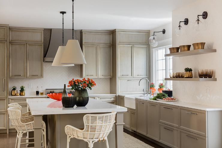 well appointed gray kitchen boasts a gray island seating cream rattan barstools in front of a white quartz countertop lit by goodman hanging lamps - Acorn Kitchen Cabinets