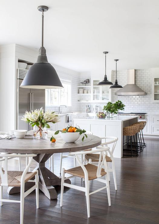 A gorgeous eat in kitchen boasts a black industrial pendant hung over a  Restoration Hardware Salvaged Wood X Base Round Dining Table surrounded by  Hans. Round Gray Salvaged Wood Kitchen Dining Table Design Ideas