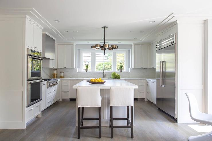 Well Appointed White U Shaped Kitchen Is Lit By An Arteriors Jalen Chandelier Hung Over A White Center Island Topped With A White Marble Countertop Seating
