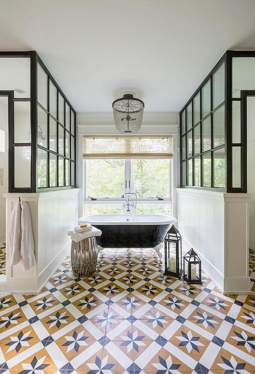 white and black clawfoot bathtub flanked by his and her showers