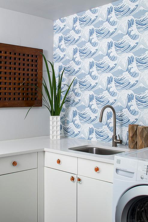 A Beach Themed Laundry Room Boasts An Accent Wall Clad In Cole U0026 Son  Frontier Wallpaper Lined With White Flat Front Cabinets Adorned With Orange  Knobs ...