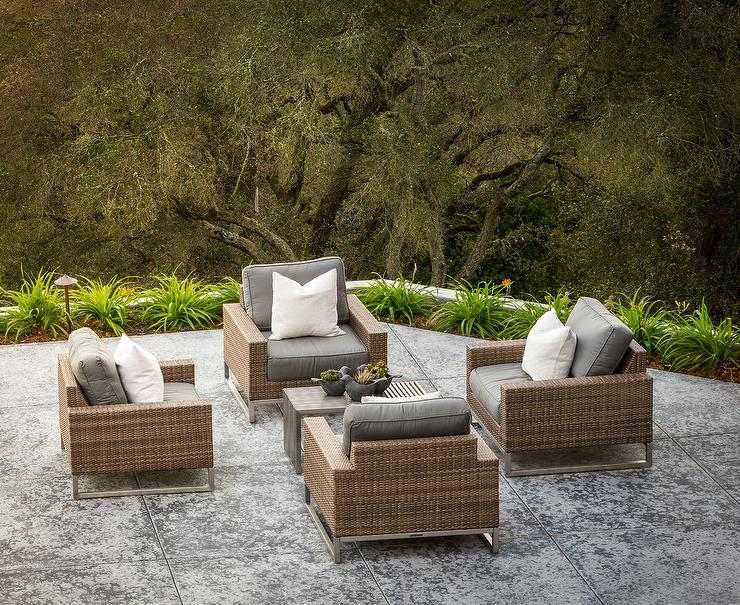 Chic Concrete Patio Is Filled With Brown Wicker Outdoor Chairs Placed In A  Circular Formation Surrounding A Gray Teak Coffee Table. Part 63