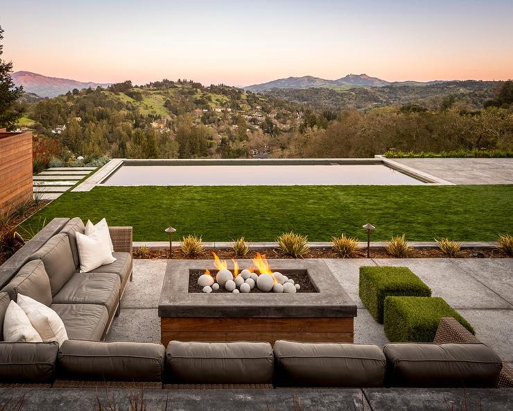 chic patio features a wicker corner sectional lined with gray outdoor seat cushions as well as two faux grass ottomans facing a wood and concrete fire pit