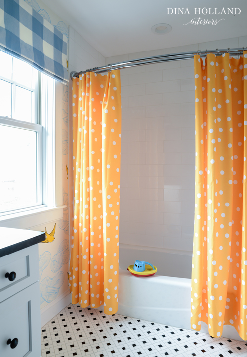 curved shower rail with orange curtains