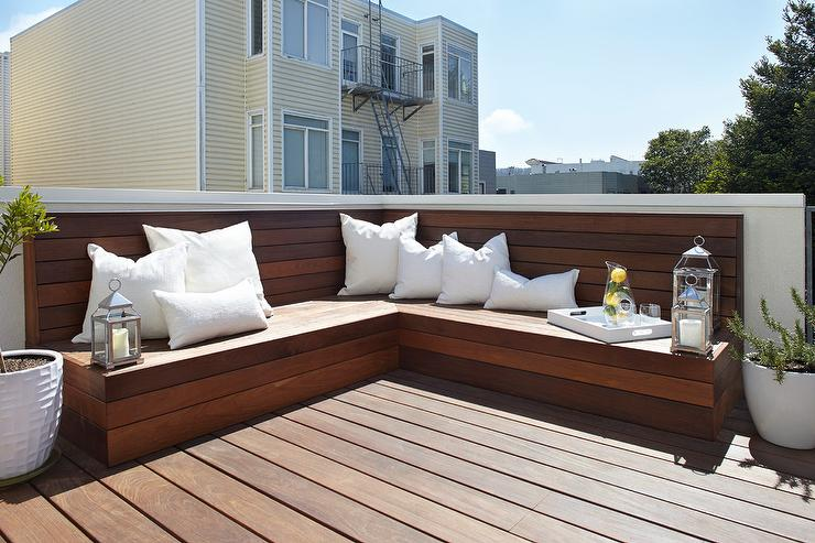 a stained deck boasting a l shaped builtin teak bench adorned with white outdoor pillows alongside plants in white planters