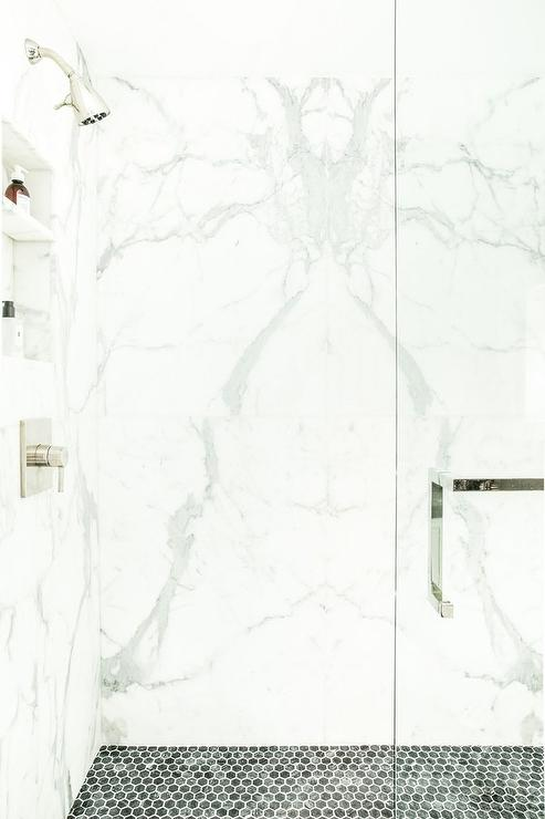 white and gray marble slabs frame the shower walls with a veined appearance while black hexagon tiles make up the floors around glass doors and chrome kit