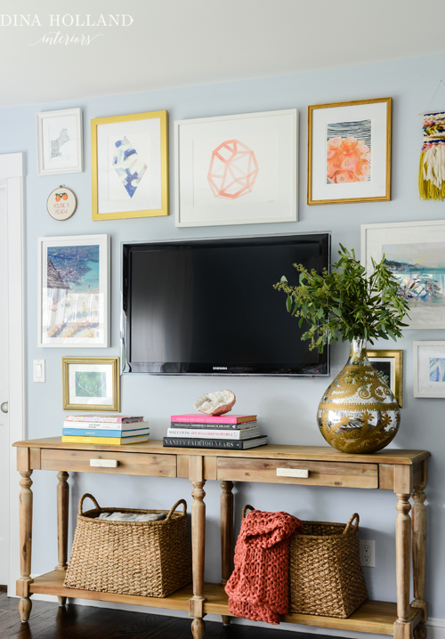 A collection of eclectic art surrounds and disguises a flat panel television  suspended over long wood console table fitted with turned legs topped with  ...