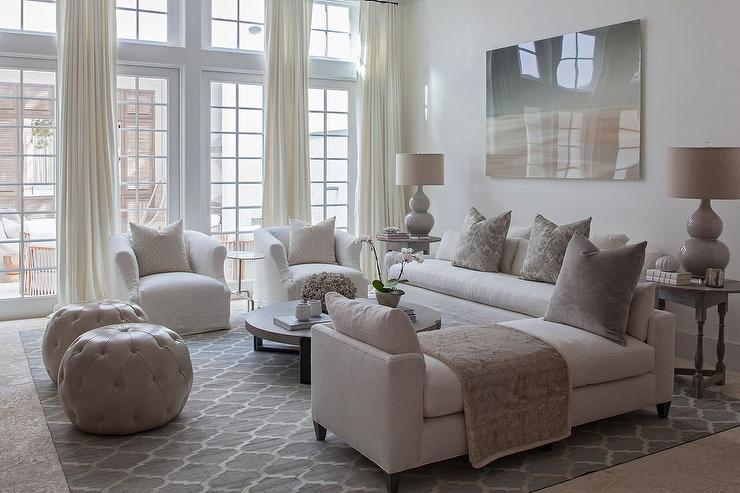 White And Ivory Living Room Boasts A Gray Abstract Art Piece Standing Over An Slipcovered Sofa Adorned With Metallic Pillows Flanked By Round