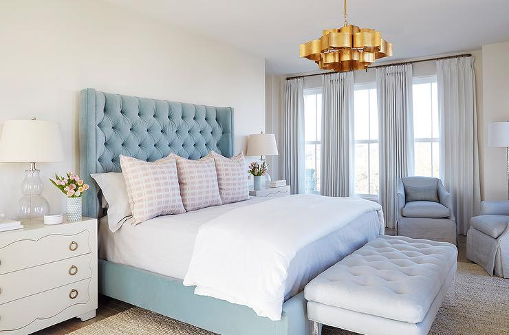 Currey Co Grand Lotus Chandelier Illuminates A Tall Blue Velvet Wingback Bed Flanked By White 3 Drawer Dressers As Nightstands Bungalow 5 Isabella Large