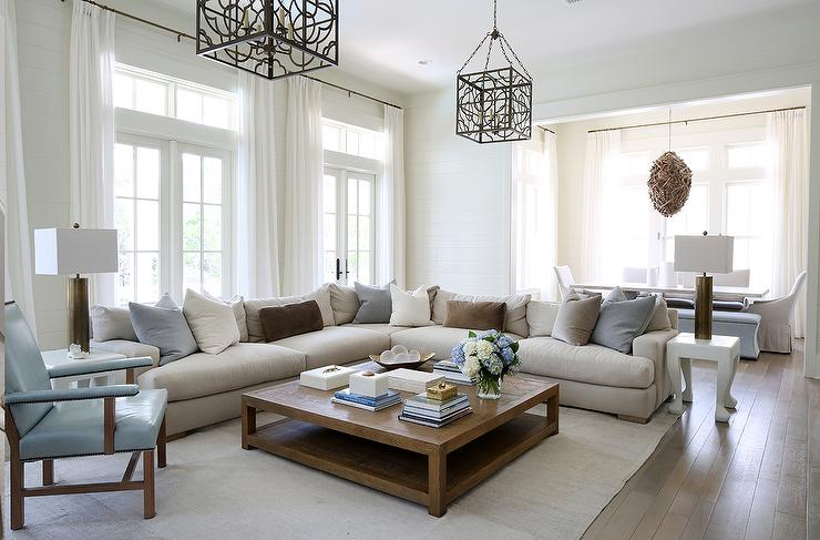 Julian Chichester Anna Lanterns Illumiante A Corner Oatmeal Linen Sectional  Lined With Brown And Blue Velvet Pillows Flanked By White Hoof End Tables  And ...