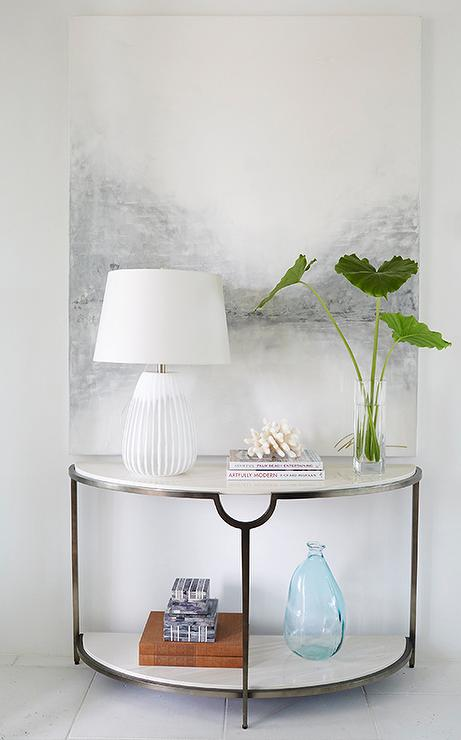 Marvelous Bright, White Foyer Features A Half Moon Marble Console Table Topped With A  White Striped Map Tucked Under A White And Gray Abstract Art Piece.