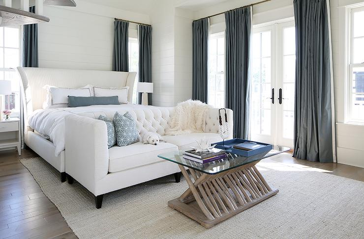 ... A White Wingback Bed Dressed In White And Black Hotel Bedding Is  Flanked By White Nightstands Placed Under Windows Dressed In Slate Blue  Silk Curtains.