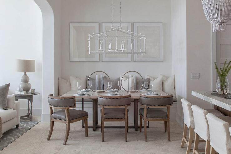 elegant dining room boasts a rectangular white birdcage chandelier a trio of framed art pieces standing over a builtin dining bench adorned - Birdcage Chandelier