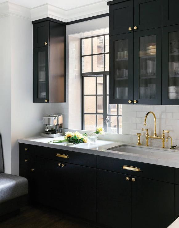 Black Kitchen Features Glass Reeded Upper Cabinets And Black Lower Cabinets  Adorned With Polished Brass Hardware Paired With White Marble Countertops  And A ...
