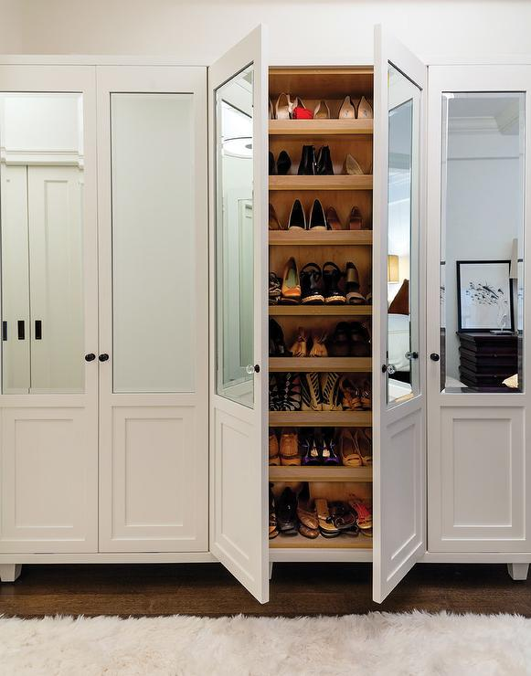 Glam Walk In Closet Boasts A Wall Of Mirrored Shoe Cabinets Lined With  Stacked Pull Out Shelves.