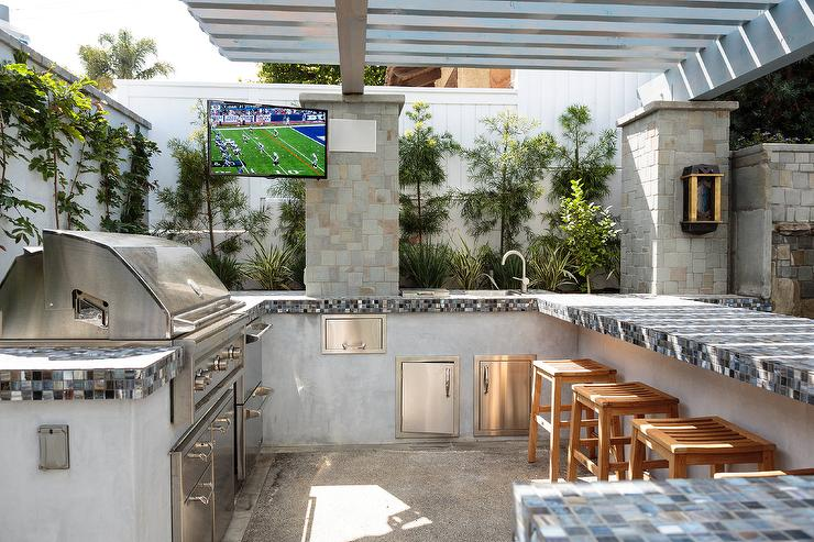 A Gray Pergola Shades A Gray Stucco Outdoor Kitchen Fitted With A Stainless Steel Bbq Grill Placed Next To Stacked Stainless Steel Refrigerator Drawers