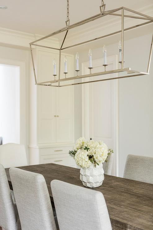 A Polished Nickel Linear Pendant Known As The Darlana Hangs Over Reclaimed Wood Dining Table With Linen Armless Chairs