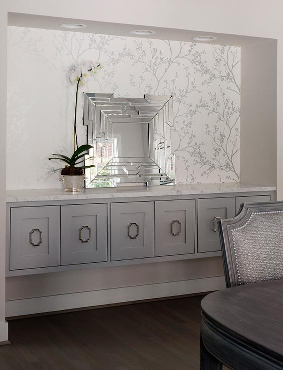 A Dining Room Nook Is Clad In Schumacher Twiggy Silver Wallpaper Lined With Leaning Fretwork Mirror Placed On Long Gray Floating Buffet Cabinet Adorned