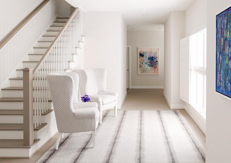 A Pair Of White And Gray Geometric Print Wingback Chairs Sit Atop A White  And Gray Rug Placed In Front Of A Gray Wash Staircase Handrail And Treads  Accented ...