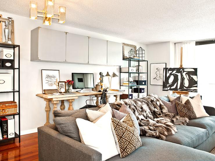Contemporary Living Room Boasts A Gray Sofa With Chaise Lounge Dressed In White Pillows Brown Greek Key And Faux Fur Throw Blanket