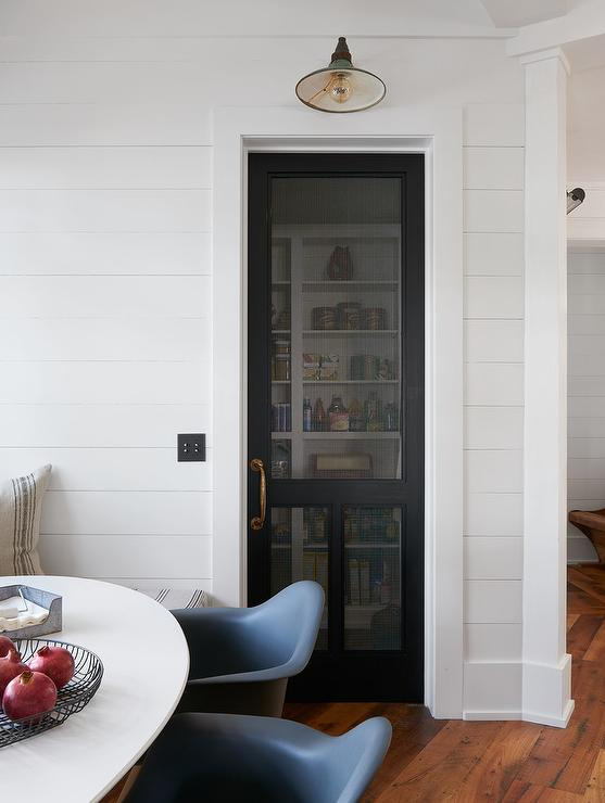Delicieux Cottage Kitchen Boasts A Shiplap Wall Fitted With A Black Mesh Screen Door  Fitted With An Antique Brass Door Handle Illuminated By A Vintage Barn  Sconce.