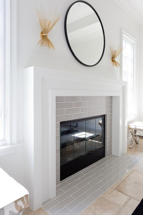 A black convex mirror is illuminated by two Kelly Wearstler Strada 2 Light Wall Sconces placed over a white art deco fireplace mantel accented with linear gray tiles.