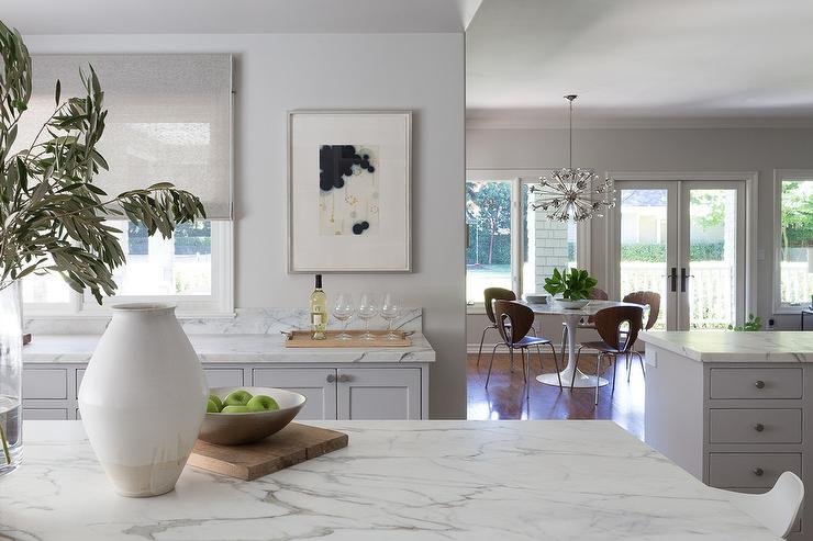 David Duncan Livingston Photography Creates A Still Of A Modern Kitchen  With A Marble Island Viewing A Long Marble Countertop With Gray Shaker  Cabinets.