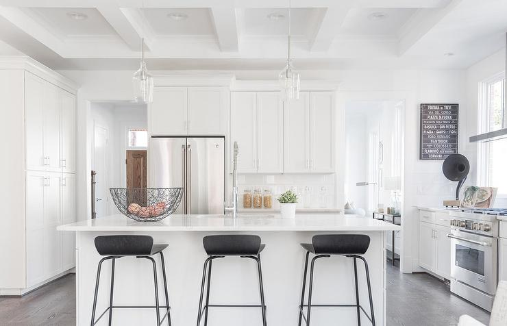 A Large U Shaped Kitchen Welcomes Lots Of Natural Light Showcasing White  Cabinetry And A Large White Kitchen Island.