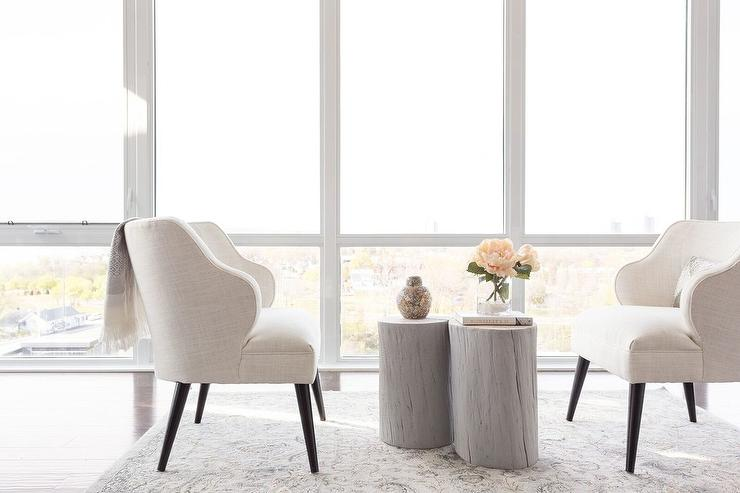 a pair of white linen wingback chairs face each other across from a pair of gray wood tree trunk tables atop a gray wool rug placed in front of floor to