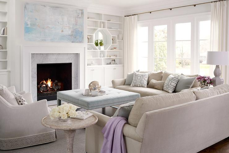 Inviting living room boasts a blue abstract canvas art piece placed over a white fireplace mantel accented with a carrera marble surround flanked by white built-in shelves fitted with octagonal mirrors as well as white shaker cabinets.